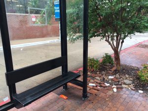 Picture of covered bus stop with candy wrapper, various discarded cups and traash